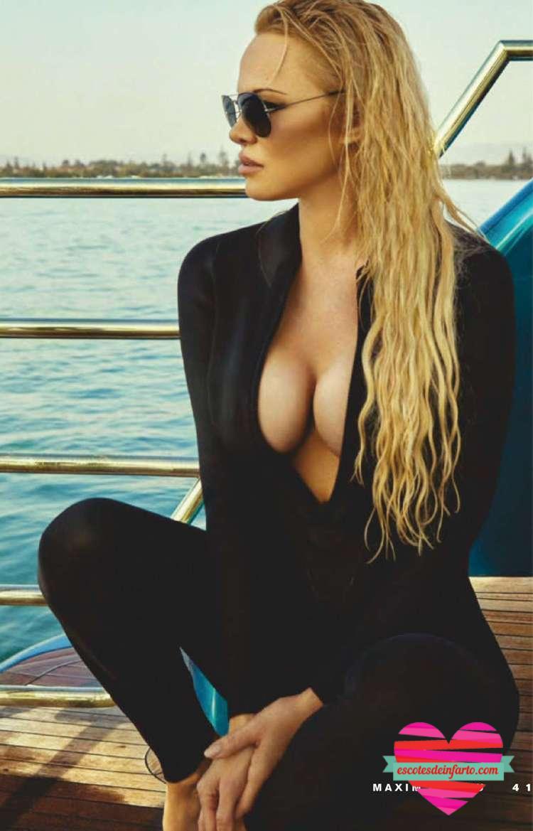 Pamela Anderson con gafas de sol y escote pronunciado sentada en un barco