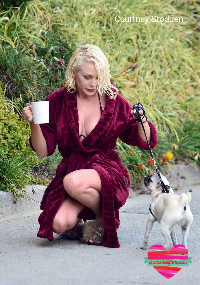 Courtney Stodden con una taza se agacha para ver al perro