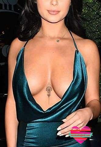 Mujer con un vestido azul de tirantas muy escotado mostrando un tatuaje pequeño bajo el pecho